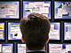 Business: Man looking at several monitors with financial data: (c) Steve Cole/Getty Images